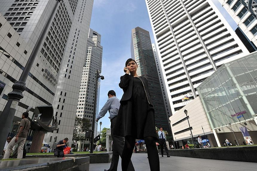 People walking outside Raffles Place MRT. More firms in Singapore are providing flexible work benefits for their staff, says the Manpower Ministry. -- PHOTO: ST FILE