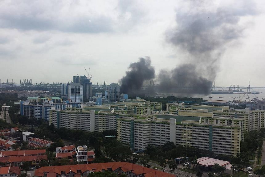 A thick, dark mass of smoke rising from the affected area at around 2.10pm, seen from a condominium in West Coast Walk. -- PHOTO: GEOFFREY DELHAYE