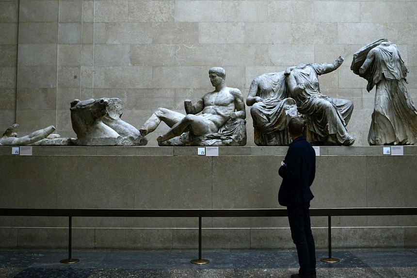 A man looks at the Parthenon Marbles, a collection of stone objects, inscriptions and sculptures, also known as the Elgin Marbles, on show at the British Museum in London on Oct 16, 2014. -- PHOTO: REUTERS