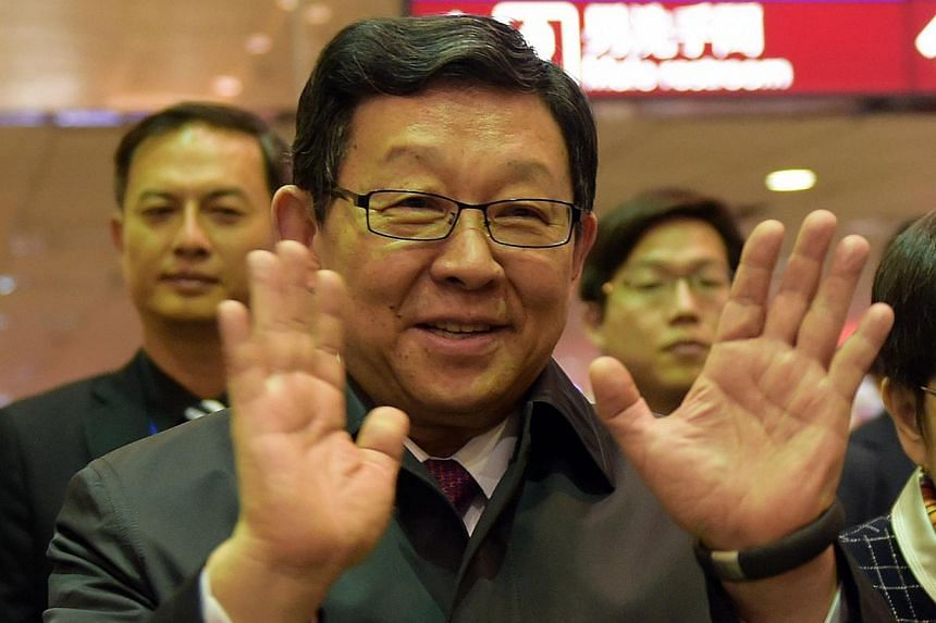 China's Taiwan envoy Chen Deming, president of the quasi-official Association for Relations Across the Taiwan Strait, waves to reporters on his arrival at Taoyuan airport on Dec 9, 2014. -- PHOTO: AFP