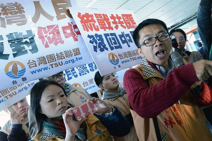Demonstrators from the opposition Taiwan Solidarity Union (TSU) is stopped by a police outside the Taoyuan airport as Chinese envoy Chen Deming arrives on Dec 9, 2014. -- PHOTO: AFP