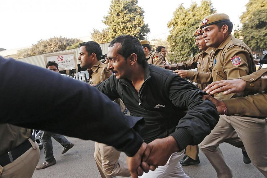 Policemen run with Uber driver Shiv Kumar Yadav (centre), who is accused of rape, outside a court in New Delhi on Dec 8, 2014. -- PHOTO: REUTERS