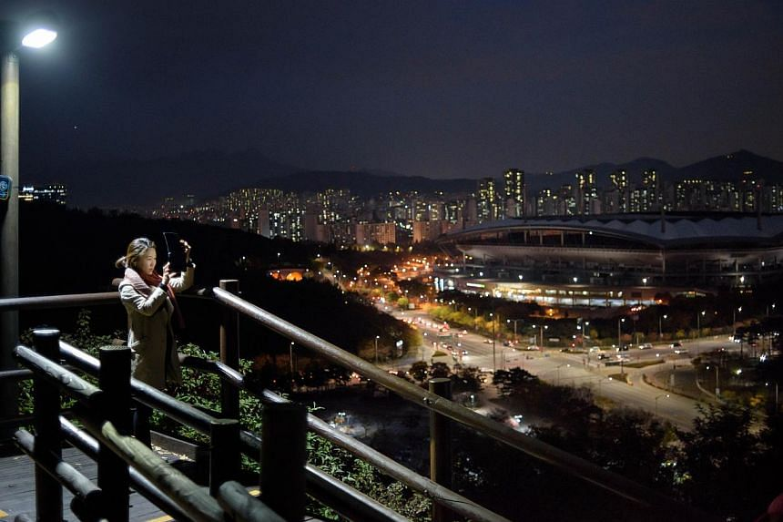 A woman takes pictures of the Seoul city skyline. South Korea's top government think-tank cut its economic growth forecasts for this year and next. --PHOTO: AFP