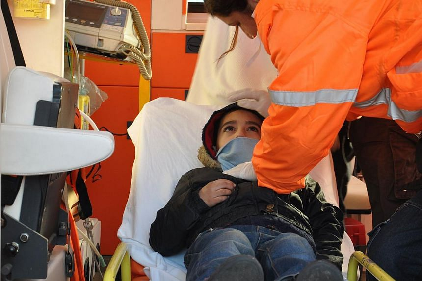 A Syrian child is given medical treatment in an ambulance after being rescued with some 200 refugees from a boat near the port of Kyrenia off the northern coast of the Turkish Republic of Northern Cyprus, after the vessel signalled for help when it h