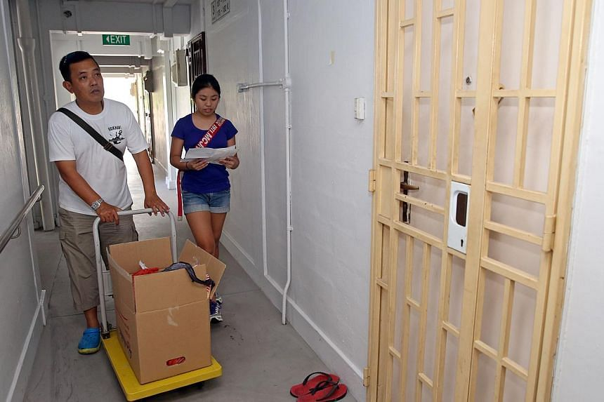 Mr Mervyn Chua, 48, and his daughter, Ryen, 12, distributing food to Madam Liow Mee Yin, 75, and other elderly folk living alone in Jalan Kukoh. The Chuas are members of Friends in Charity, an informal group of volunteers who give food and cash to ab