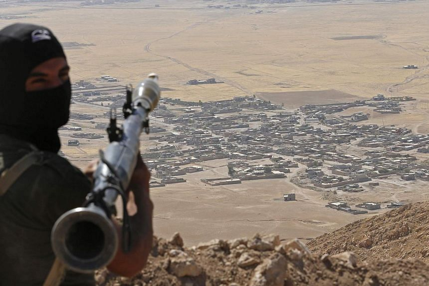 A Kurdish fighter watches Baretle village, which is controlled by the Islamic State, in Khazir, on the edge of Mosul, in this Sept 8, 2014 file photo. -- PHOTO: REUTERS
