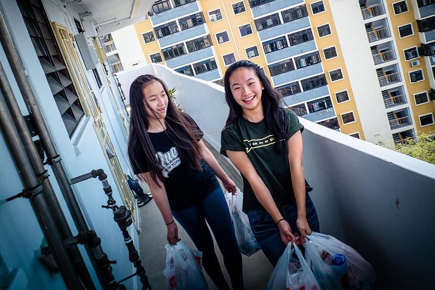 Young volunteers Chaire Phua (left), 15, and Celest Ling, 15, on their rounds to distribute the food bags to rental flat households. Under Project Home Sweet Home, younger residents in Jalan Kukoh estate get their goodie bags of food items only if th