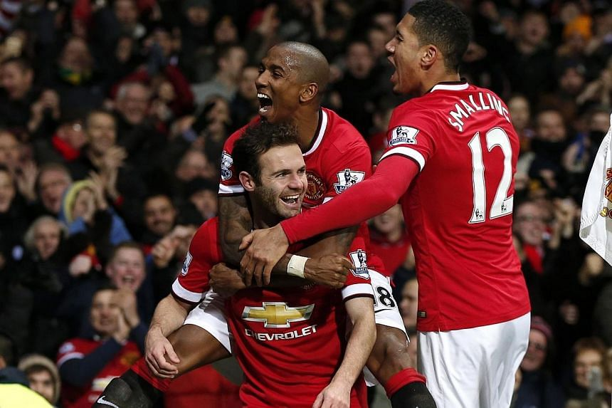 Manchester United's Juan Mata (centre) celebrates with Ashley Young and Chris Smalling (right) after scoring his team's second goal during their English Premier League soccer match against Stoke City at Old Trafford in Manchester, northern England, o