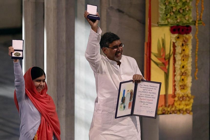 Nobel Peace Prize laureates Kailash Satyarthi and Malala Yousafzai with their Nobel Prize medals during the Nobel Peace Prize awards ceremony at the City Hall in Oslo on Dec 10, 2014. -- PHOTO: AFP