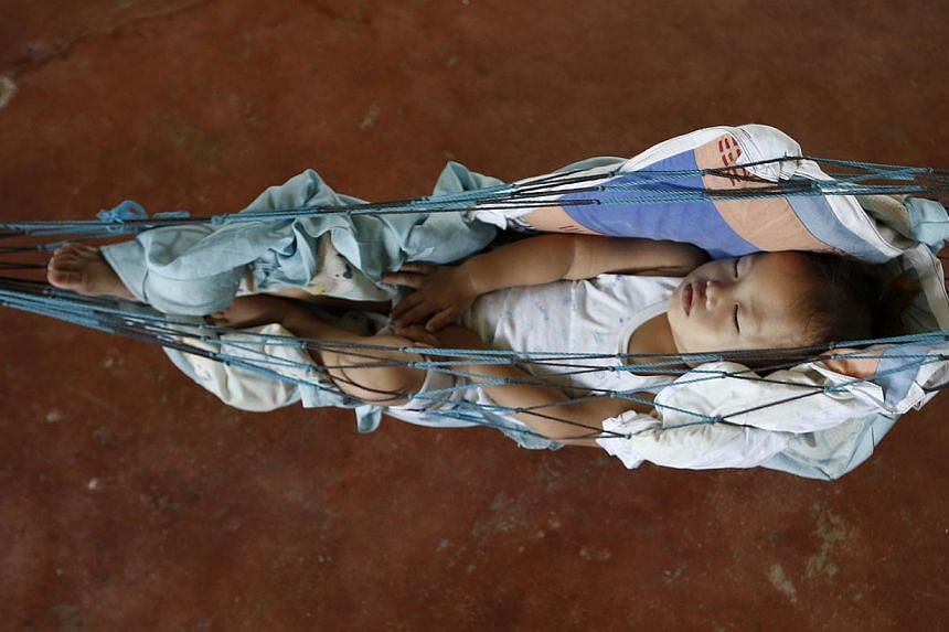 A baby sleeps in a hammock at an evacuation centre for Typhoon Hagupit victims in San Julian, Eastern Samar in central Philippines. Emergency workers were struggling on Tuesday to reach coastal villages on an island hardest hit by a typhoon. Nearly 1