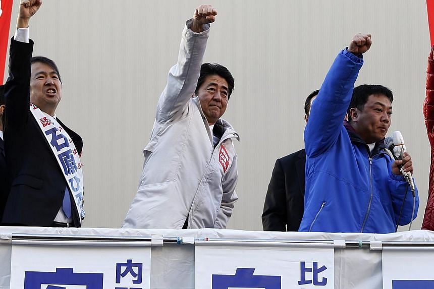 Japan's Prime Minister Shinzo Abe (centre) raises his fist with a candidate and supporters atop a van during a campaign for the Dec. 14 lower house election in Tokyo on Sunday December 7, 2014. On Tuesday, Abe announced that Apple would build one of