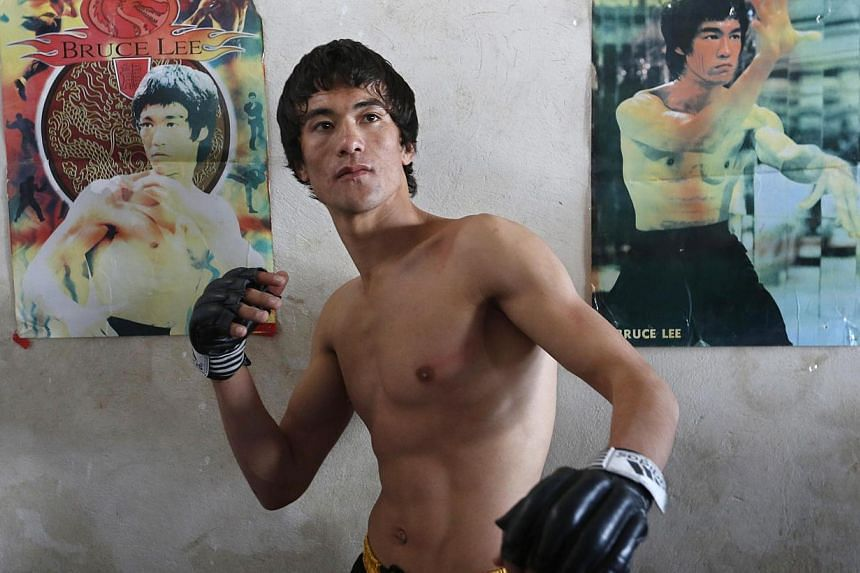 Mr Abbas Alizada, who calls himself the Afghan Bruce Lee, posing for a picture in front of the gongfu legend's posters after exercising in Kabul on Dec 9, 2014. -- PHOTO: REUTERS