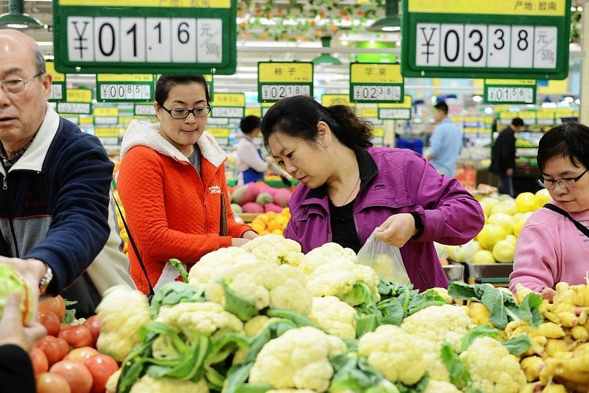 Customers choose vegetables in a market in Qingdao, east China's Shandong province, on Nov 10, 2014. -- PHOTO: AFP