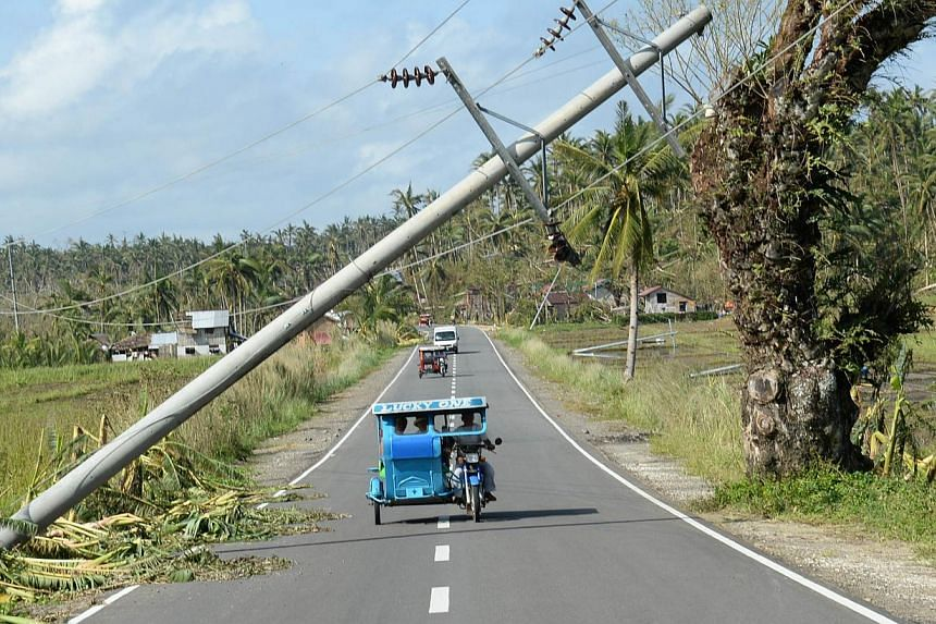 A tricycle speeds past a fallen electric pylon destroyed by Typhoon Hagupit along the national highway in San Julian town, Eastern Samar province, on Dec 9, 2014. A joint congressional panel has approved a 15 per cent increase in the government's nat