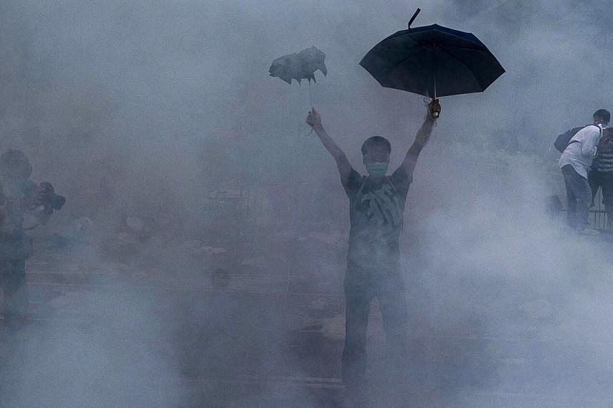 A pro-democracy demonstrator gestures after police fired tear gas towards protesters near the Hong Kong government headquarters on Sept 28, 2014. -- PHOTO: AFP