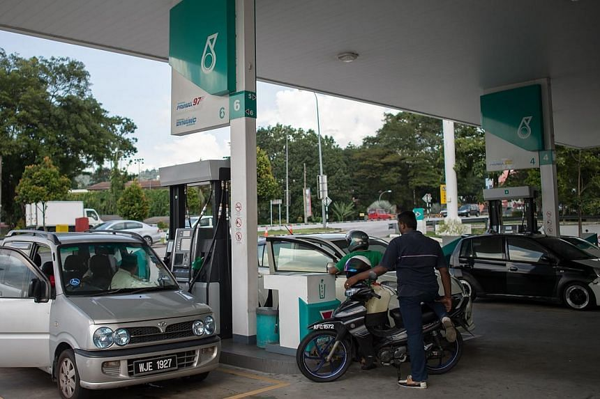 People waiting to refill their vehicles at a Petronas petrol station in Ampang on Nov 28, 2014. Malaysian state oil company Petronas warning last month that its contribution to public coffers could fall from RM68 billion (S$25.8 billion) - which was