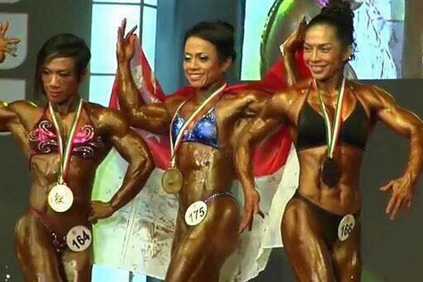 Singapore's Sue Suharni (centre)bagged gold in the women's bodybuilding eventat the recently concluded World Body Building & Physique Sports Championships in Mumbai.-- PHOTO:WBPF