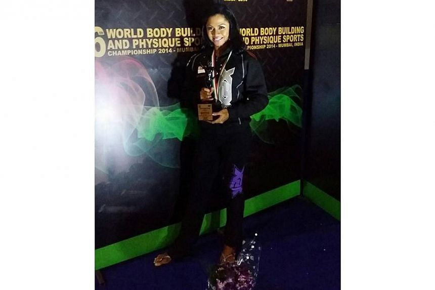 Singapore's Rinn Farina celebrates her win in the women's athletic physique 165cm category at the 6thWorld Body Building & Physique Sports Championshipsheld in Mumbai, India. -- PHOTO:WBPF