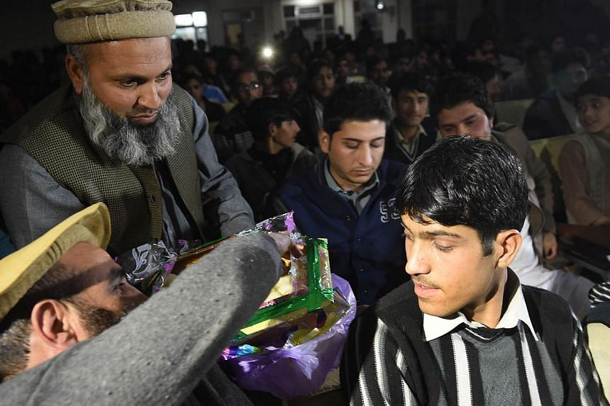 Pakistan residents disribute sweets as they watch a live broadcast of the award ceremony of joint Nobel Peace Prize laureate, Malala Yousafzai at a school hall in her home town of Mingora, a district of Swat valley on Dec 10, 2014. Hundreds of reside