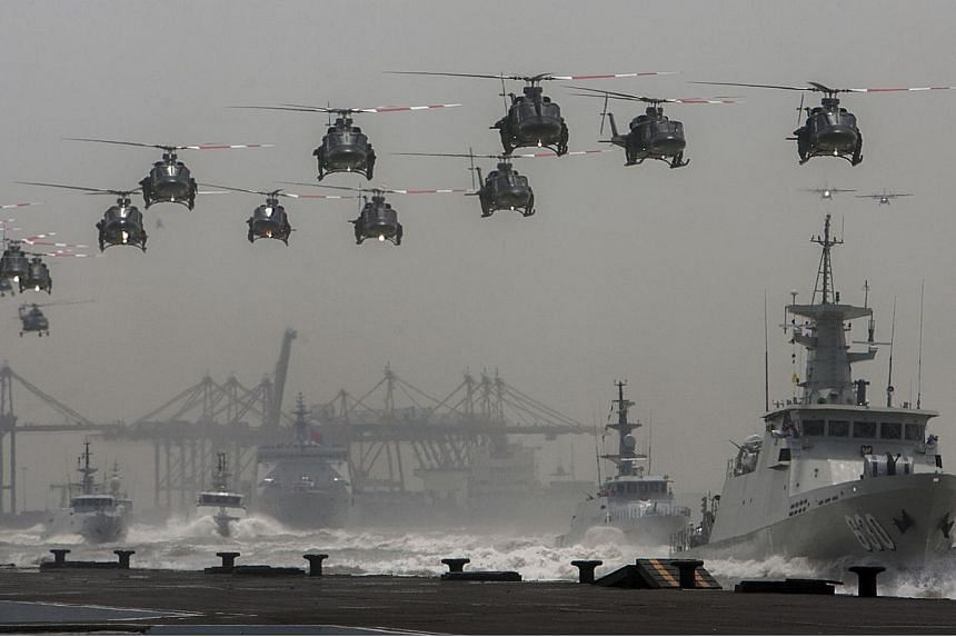 Indonesian helicopters fly over navy ships sailing in formation during the celebration of the 69th anniversary of the Indonesian armed forces on Oct 7, 2014. -- PHOTO: AFP