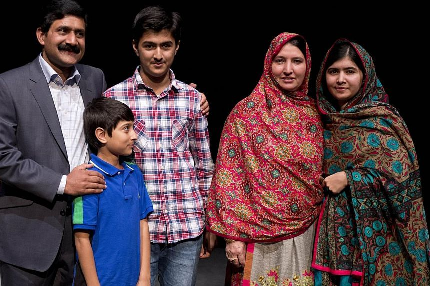 Pakistani rights activist Malala Yousafzai (right) with her family after addressing the media in Birmingham, central England, on Oct 10, 2014. -- PHOTO: AFP