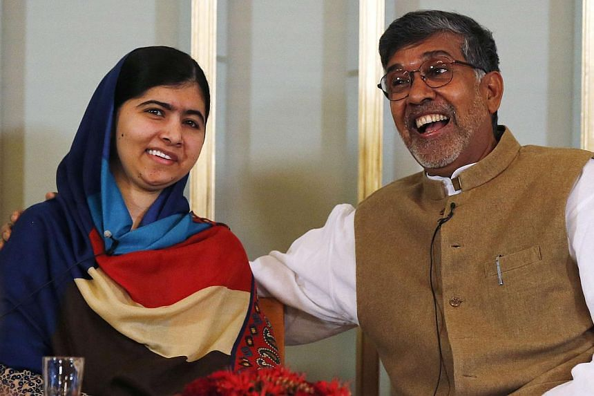 Nobel Peace Prize laureates Kailash Satyarthi (right) and Malala Yousafzai at a news conference in Oslo, Norway, on Dec 9, 2014. -- PHOTO: REUTERS