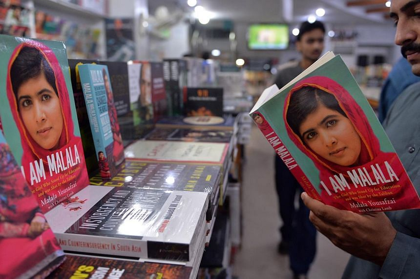 A Pakistani customer looks at the autobiography of Malala Yousafzai at a bookstore in Islamabad, Pakistan, on Oct 10, 2014. -- PHOTO: AFP