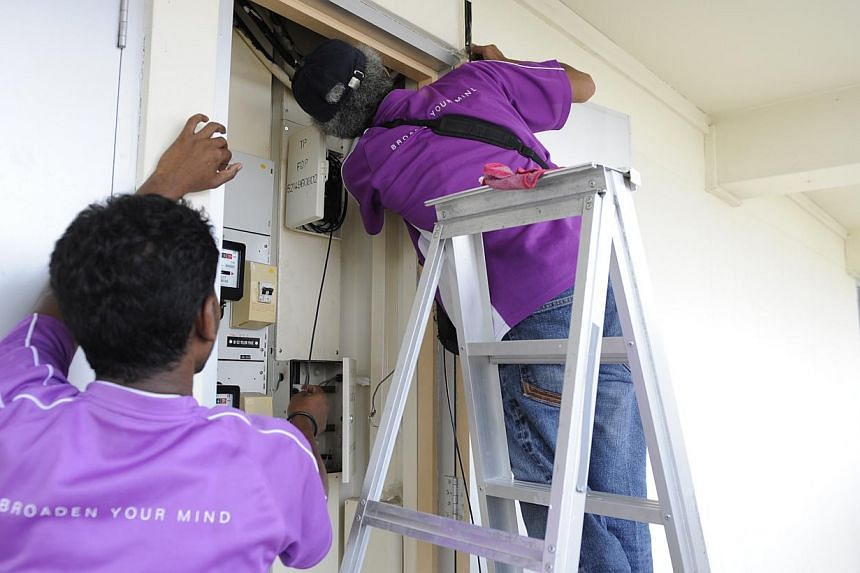 Contractors installing the OpenNet cable in the Tampines estate. NetLink Trust, formerly OpenNet, was fined $50,000 for failing to meet its standards for delivering home users' fibre orders during the first six months of this year. -- ST PHOTO: ASHLE