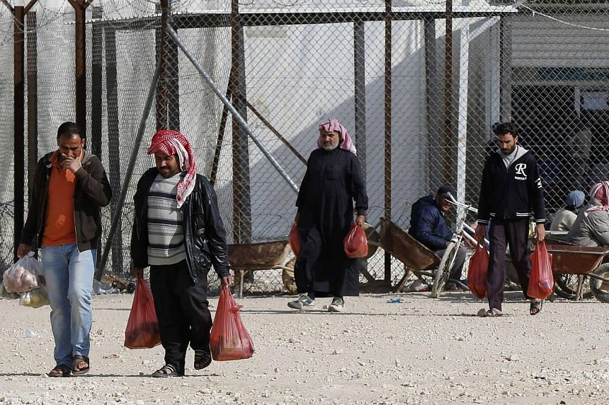 Syrian refugees leave after shopping with humanitarian aid vouchers at refugee camp in the Jordanian city of Mafraq, near the border with Syria, Dec 7, 2014. Countries have more than doubled the number of Syrian refugees they are willing to rese