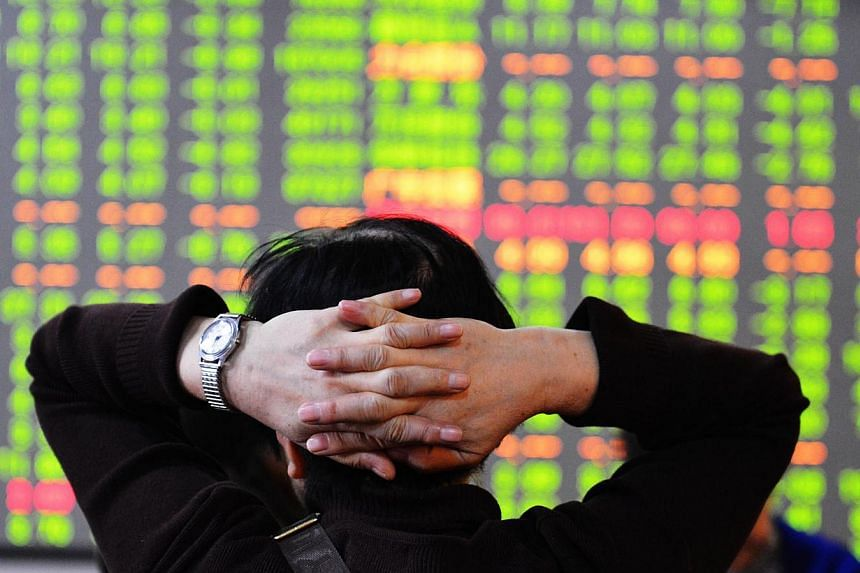 A stock investor checks the share prices at a security firm in Hangzhou, east China's Zhejiang province on Dec 9, 2014. Investors sold equities worldwide on Tuesday after China's market posted its worst day in five years and oil prices fell to l