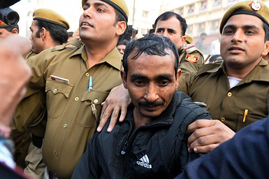 Indian police escort Uber taxi driver Shiv Kumar Yadav (centre), who is accused of rape, following his court appearance in New Delhi on Dec 8, 2014. -- PHOTO: AFP
