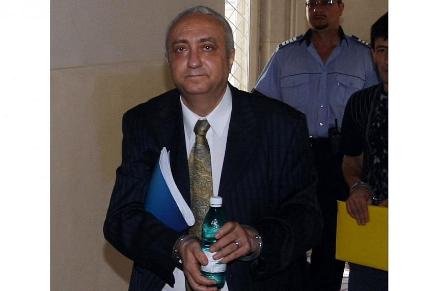 The former business attache of Romania to Singapore, Silviu Ionescu, walks out of court in handcuffs after a hearing, on July 27, 2010, in Bucharest. -- PHOTO:LIBERTATEA