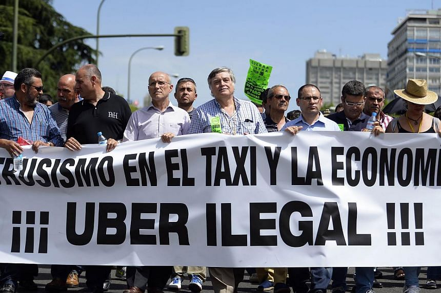 A file picture taken on June 11, 2014 shows taxi drivers carrying a banner during a strike action in protest of unlicensed taxi-type-services in central Madrid. A judge on Dec 9, 2014 banned the popular US cellphone-based taxi service Uber from opera