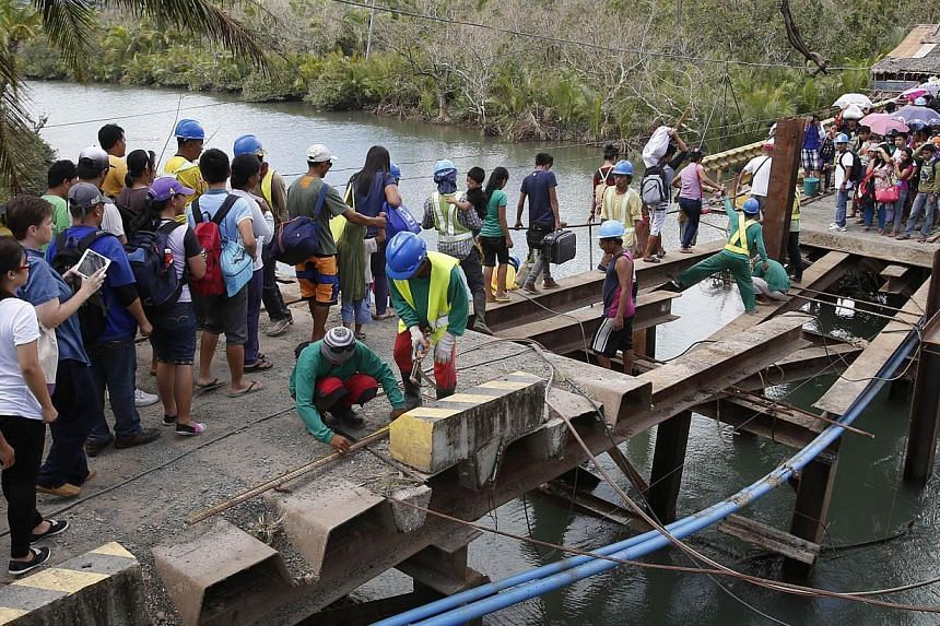 Residents cross a bridge, which was damaged by Typhoon Hagupit, in San Julian, Eastern Samar in central Philippines on Dec 10, 2014. -- PHOTO: REUTERS