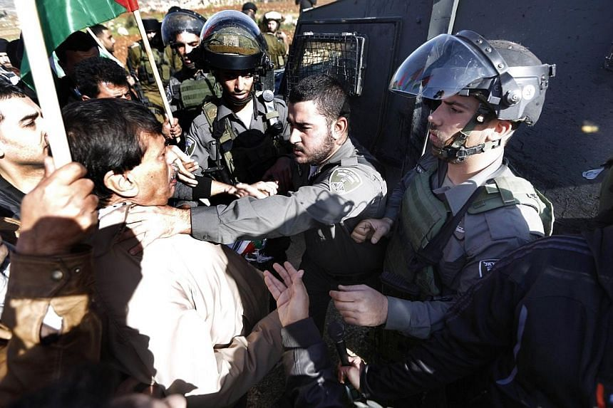 An Israeli border guard grabs Palestinian official Ziad Abu Ein (left), in charge of the issue of Israeli settlements for the Palestinian Authority, during a demonstration in the village of Turmus Aya near Ramallah, on Dec 10, 2014.The Palestin