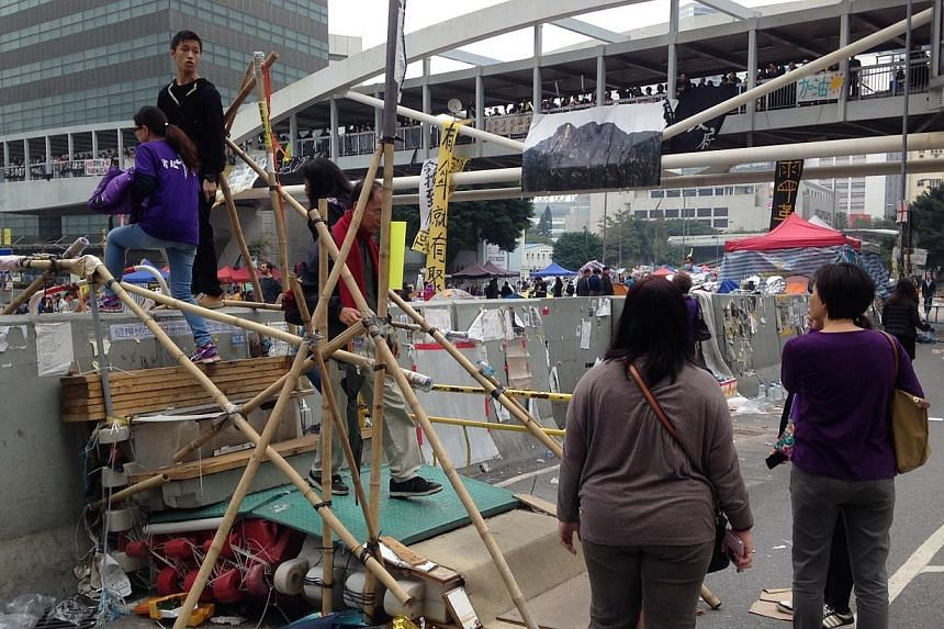 Abandoned tents and equipment left behind by protesters in the Admiralty district of Hong Kong on Dec 11, 2014. A few protesters were seen milling about despite police orders to leave. -- ST PHOTO: CHONG ZILIANG