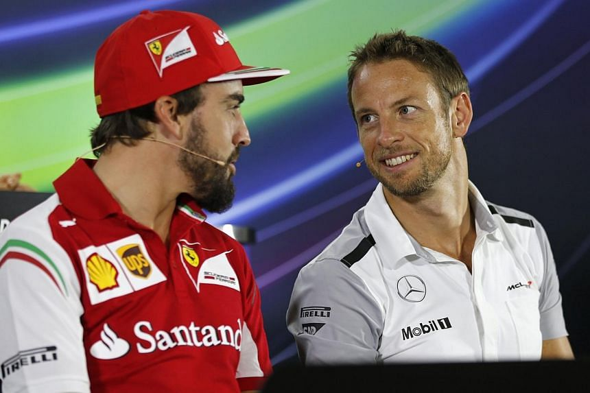 Ferrari Formula One driver Fernando Alonso of Spain (left) talks with McLaren Formula One driver Jenson Button of Britain during a news conference at the Yas Marina circuit, before the start of the Abu Dhabi Grand Prix on Nov 20, 2014. -- PHOTO: