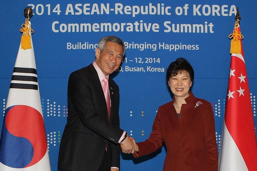 South Korea's President Park Geun Hye (right) shakes hands with Singapore's Prime Minister Lee Hsien Loong during their bilateral meeting at the Asean-Republic of Korea Commemorative Summit in Busan on Dec 11, 2014. PM Lee and President Park rea