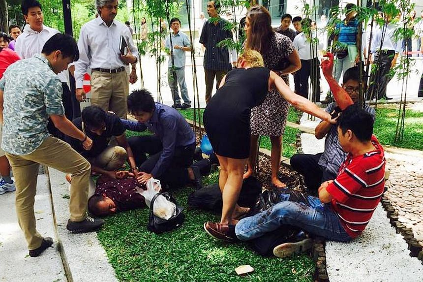 Members of the public attending to Indonesian businessman Kang Tie Tie, who was wounded in the abdomen and right arm in an armed robbery at Raffles Place on Nov 14, 2014. -- PHOTO: LEON LEE