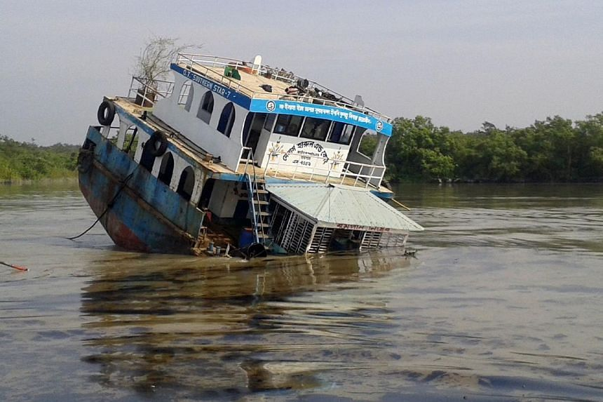 A Bangladeshi oil tanker lies half-submerged after it was hit by a cargo vessel on the Shela River in the Sundarbans in Mongla on Dec 9, 2014. Bangladesh officials warned Thursday, Dec 11, that the oil spill  is threatening endangered dolph
