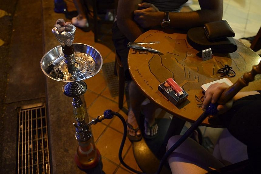 """A customer smokes a shisha or """"hookah"""" pipe at a cafe on Bussorah Street on Nov 4, 2014.Singapore appears to be alone in its ban on shisha, the sweet-smelling tobacco product that is smoked socially in several parts of the world. -- PHOTO: ST F"""