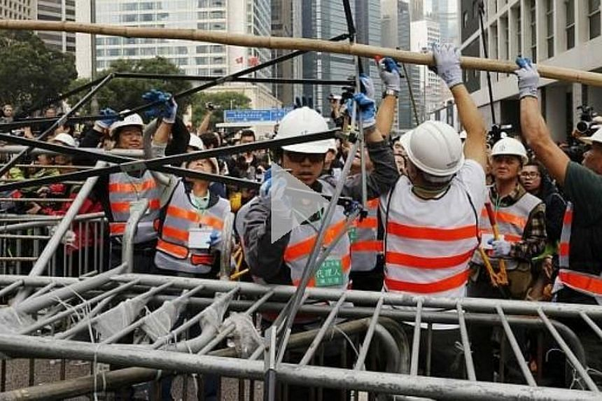 Workers remove a barricade at an area blocked by pro-democracy protesters near the government headquarters building at the financial Central district in Hong Kong on Dec 11, 2014. -- PHOTO: REUTERS