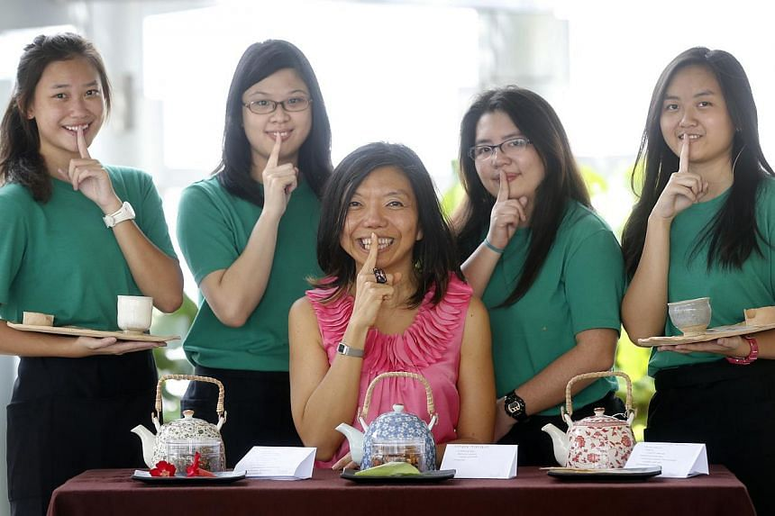 Hush founder Anthea Ong (centre), 46, with her tea servers (from left) Sebrina Ng, 18, Teo Sing Yi, 23, Grace Ng, 30, and Adeline Soo, 17. The social enterprise's 10 deaf tea servers go to workplaces to guide executives through a tea-drinking session