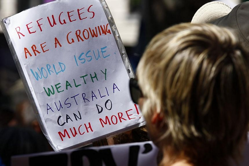 Protesters hold placards at the 'Stand up for Refugees' rally held in central Sydney, Australia on Oct 11, 2014. -- PHOTO: REUTERS
