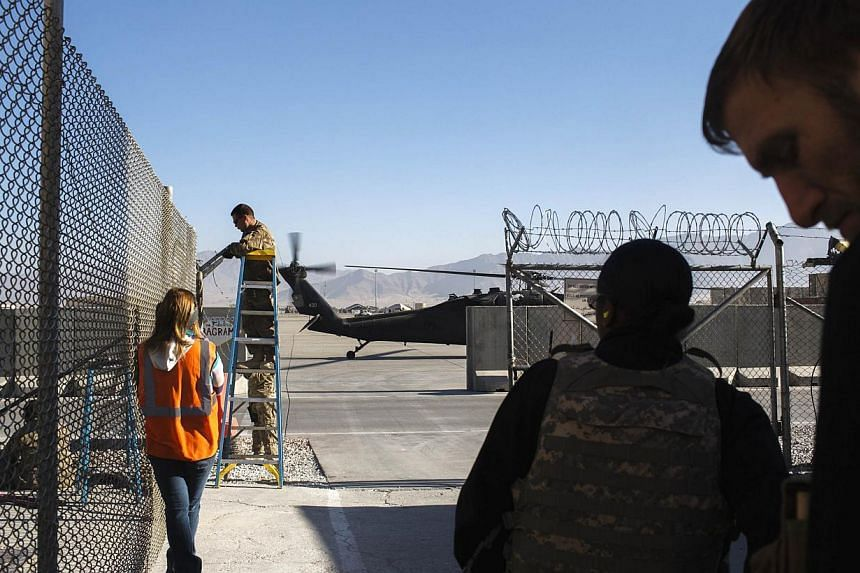 A soldier repairs barbed wire fencing while contractors await a helicopter flight at Bagram Air Base in Afghanistan Dec 10, 2014. The United States closed the Bagram detention facility on Dec 10 and no longer has custody of any detainees in Afghanist