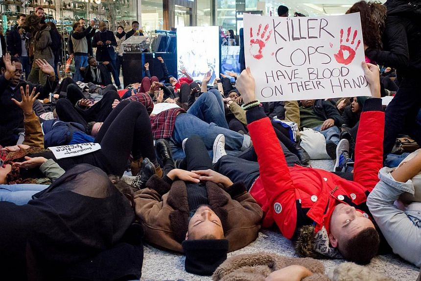 """A group of protesters create a """"die-in"""" at the Westfield shopping mall in West London on Dec 10, 2014, in support of protests in the US over the killings of black suspects by white police officers. -- PHOTO: AFP"""
