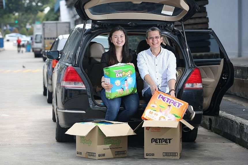 Ms Desiree Yang, 20, and her father Roland Yang, 55, set up Saltsteps, a social supermarket that sells goods rejected by regular supermarkets – for example, goods with damaged packaging or incorrect labelling – to low-income families. -- ST PHOTO
