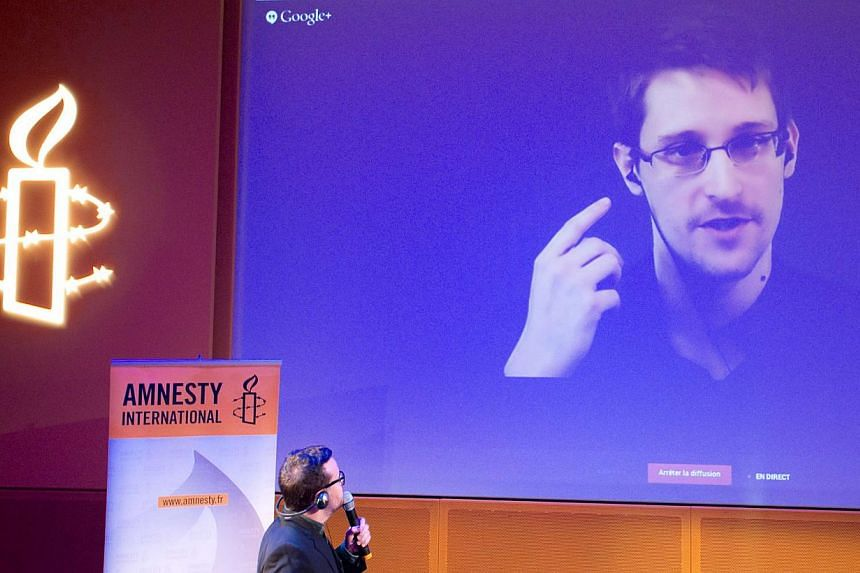 Former US National Security Agency contractor Edward Snowden, who is in Moscow, is seen on a giant screen during a live video conference for an interview as part of Amnesty International's annual Write for Rights campaign at the Gaite Lyrique in Pari