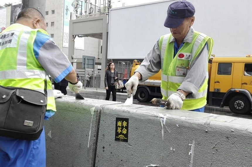 Cleaners scraping off Occupy stickers. -- PHOTO: PEARL LIU