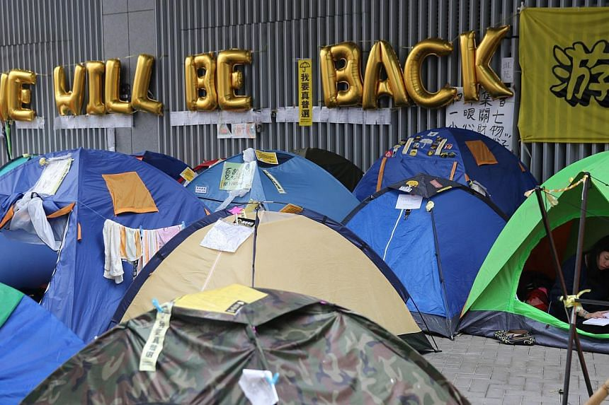 """A protester reads a book in her tent at the main anti-government protest site next to a sign that reads """"We Will Be Back"""" in the Admiralty district of Hong Kong on Dec 10, 2014. -- PHOTO: AFP"""